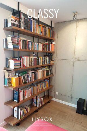 regał industrialny na książki z 7 drewnianymi półkami i konstrukcją z rurek na tle betonowej ściany