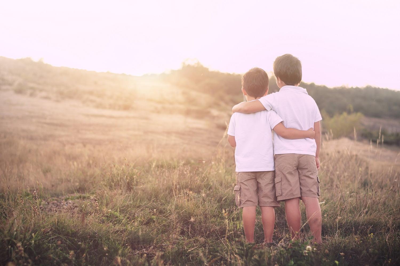 dwóch chłopców na tle wschodzącego słońca