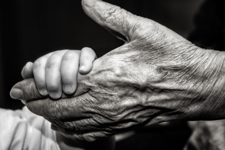 ręka dziecka trzymająca rękę starego człowieka