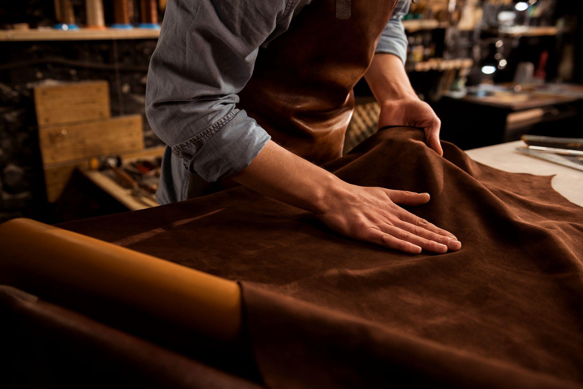 pracownik wykonujący rozkrój skóry do tapicerowania mebla